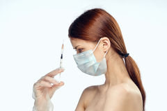 Young beautiful woman in a medical mask holds a syringe on a white insulated background, portrait.  Stock Photos