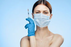 Young beautiful woman in a medical mask on a light blue background holds a syringe, portrait.  Royalty Free Stock Photography