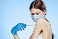 Young beautiful woman in medical mask and wearing gloves posing an injection on a blue background.  Stock Photos
