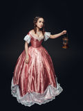 Young beautiful woman in medieval dress with lamp on black Stock Photography