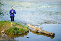 Young Beautiful Woman Meditate on the River Royalty Free Stock Photography