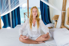 The young beautiful woman meditates on beds Royalty Free Stock Photo