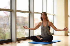 Young beautiful woman meditating in the lotus position in gym Stock Images