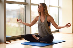 Young beautiful woman meditating in the lotus position in gym Royalty Free Stock Photos