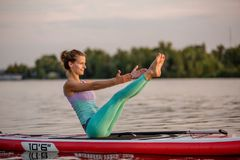 Young beautiful woman meditating in a sea at SUP paddleboarding. Healthy lifestyle. Girl in yoga pose relaxing in calm water stock image
