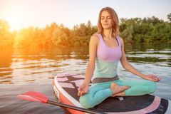 Young beautiful woman meditating in a sea at SUP paddleboarding. Healthy lifestyle. stock photo