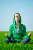 Young beautiful woman meditation. At the green field Royalty Free Stock Images