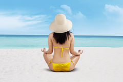 Young beautiful woman meditation on beach Stock Photography