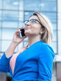 Young beautiful woman with a mobile outdoor. Royalty Free Stock Image