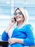 Young beautiful woman with a mobile outdoor. Royalty Free Stock Photography