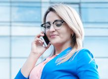 Young beautiful woman with a mobile outdoor. Royalty Free Stock Photos