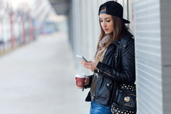 Young beautiful woman with mobile phone and coffee. Royalty Free Stock Images