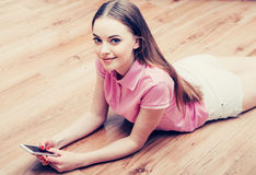 Young beautiful woman with mobile phone on floor home surfing internet Royalty Free Stock Image