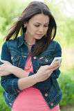 Young Beautiful woman with mobile phone outdoors Royalty Free Stock Images