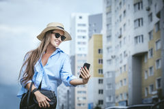 Young beautiful woman model lady fancy shirt and hat with a mobile phone on a city street royalty free stock images