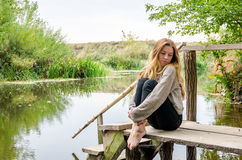 Young beautiful woman model with long blond hair sitting with different emotions laughter, sadness, sorrow, thoughtfulness on a wo Stock Photo