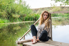 Young beautiful woman model with long blond hair sitting with different emotions laughter, sadness, sorrow, thoughtfulness on a wo Royalty Free Stock Image