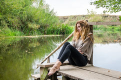 Young beautiful woman model with long blond hair sitting with different emotions laughter, sadness, sorrow, thoughtfulness on a wo Royalty Free Stock Photo