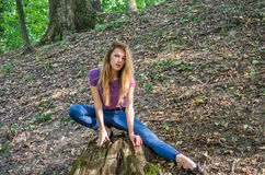 Young beautiful woman model with long hair in jeans and a tank top walks through the forest park among trees and vegetation posing Royalty Free Stock Photos