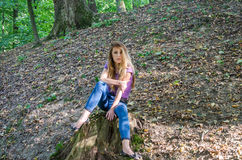 Young beautiful woman model with long hair in jeans and a tank top walks through the forest park among trees and vegetation posing Stock Photos