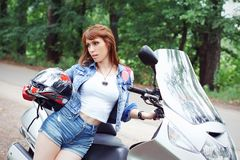 Young beautiful woman with a motorcycle outdoors. In summer Royalty Free Stock Image