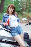Young beautiful woman with a motorcycle outdoors. In summer Royalty Free Stock Photo