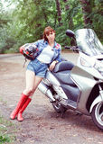 Young beautiful woman with a motorcycle outdoors. In summer Royalty Free Stock Photos