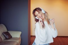 Young beautiful woman music lover. Portrait of attractive girl in headphones with phone, apps for listening to music Royalty Free Stock Photography