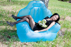 A young beautiful woman on nature by a canicular sunny day sits. In an arm-chair Royalty Free Stock Photography