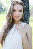 Young beautiful woman near the tree. Dreamy beautiful young woman near the tree Royalty Free Stock Photo