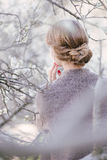 Young beautiful woman near trees in blossom in spring. Hair style bound Stock Photo