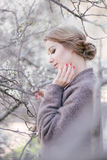 Young beautiful woman near trees in blossom in spring. Hair style bound Royalty Free Stock Photography