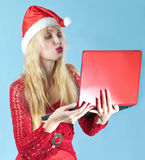 The young beautiful woman in a New Year s hat. The young beautiful woman in a New Year's hat  with  red laptop Royalty Free Stock Photo