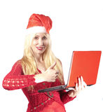 Young beautiful woman in a New Year's hat  with  red laptop. The young beautiful woman in a New Year's hat  with  red laptop Stock Photography