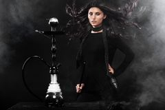 Young, beautiful woman in the night club or bar smoke a hookah or shisha. The pleasure of smoking. Sexy smoke. Stock Photo
