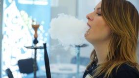 Young, beautiful woman in the night club or bar smoke a hookah or shisha. The pleasure of smoking. stock video