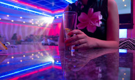 Young beautiful woman in the nightclub. With glass of drink royalty free stock photography