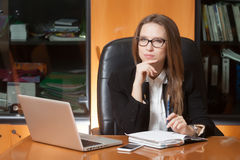 Young beautiful woman in office. Young beautiful girl sitting on the black leather chair looking into laptop display Royalty Free Stock Image