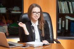 Young beautiful woman in office. Young beautiful woman sitting on the black leather chair looking forward and thinking Royalty Free Stock Photo