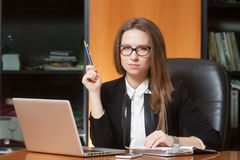 Young beautiful woman in office. Young beautiful woman sitting on the black leather chair looking into laptop display Royalty Free Stock Image