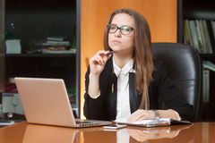 Young beautiful woman in office. Young beautiful woman sitting on the black leather chair looking into laptop display Stock Photos