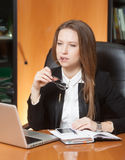Young beautiful woman in office. Young beautiful woman sitting on the black leather chair looking into laptop display Royalty Free Stock Images