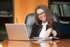 Young beautiful woman in office. Young beautiful woman sitting on the black leather chair looking into laptop display and smiling Stock Photo