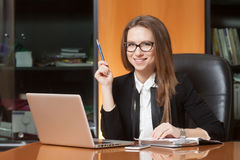 Young beautiful woman in office. Young beautiful woman sitting on the black leather chair smiling and takin pencil in hand Royalty Free Stock Image