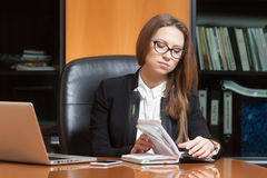 Young beautiful woman in office. Young beautiful woman sitting on the black leather chair writing something in notebook Stock Photo