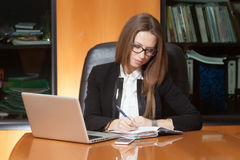 Young beautiful woman in office. Young beautiful woman sitting on the black leather chair writing something in notebook Stock Image