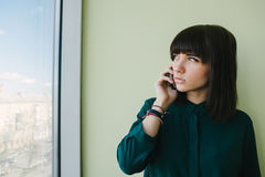 Young beautiful woman office worker talking on the phone and looking in the window. Young business woman in a dark shirt standing in modern office with phone in Stock Images
