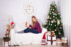 Young beautiful woman opening Christmas gift box in living room Royalty Free Stock Images