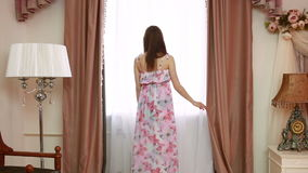Young beautiful woman opening curtains in a bedroom stock video footage