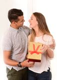 Young Beautiful Woman opening Present of her Handsome man Stock Image